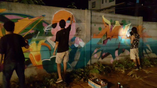 Grafitti writers tengah melukis sebuah tembok pagar di Kota Cilegon. (Foto : Gilang)